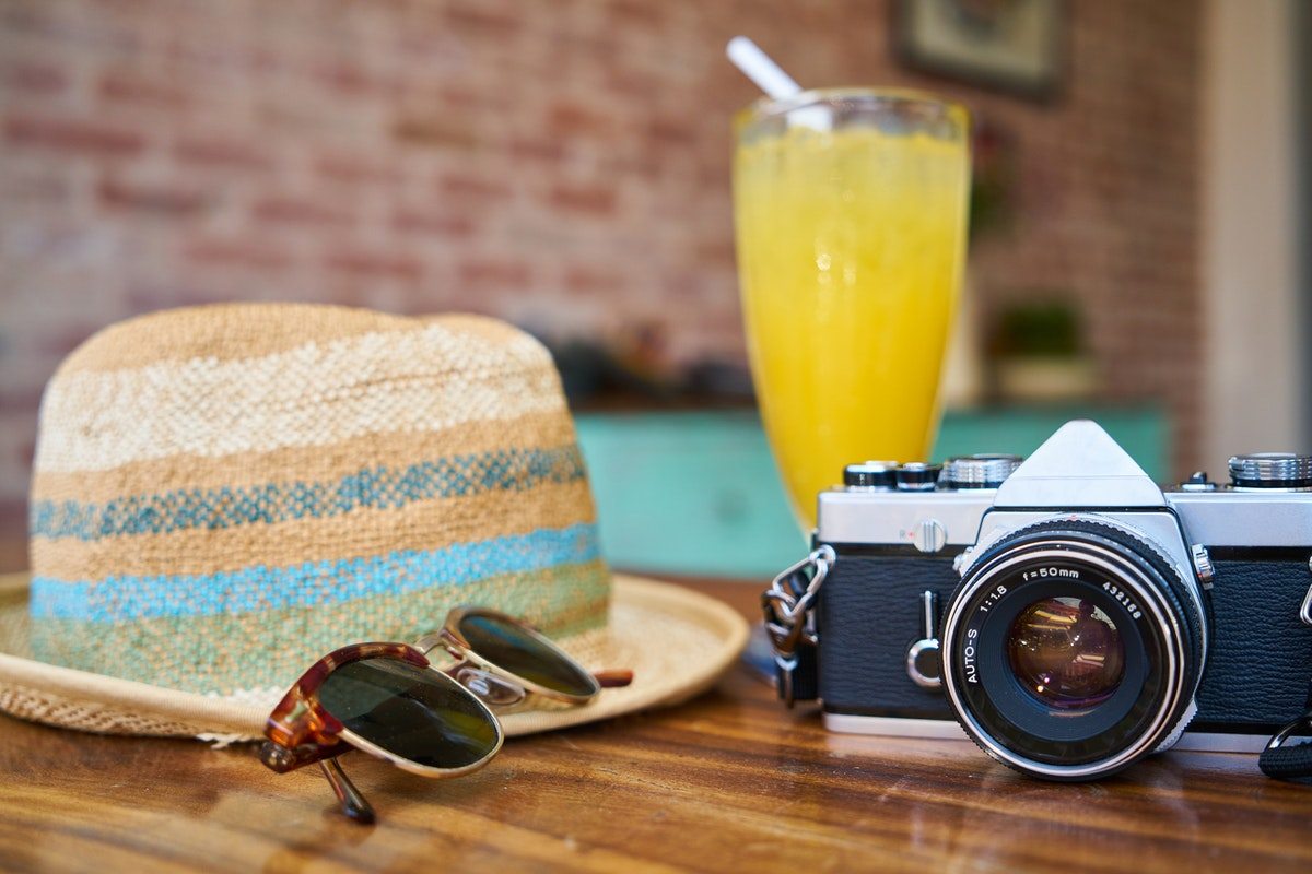Gray and Black Dslr Camera Beside Sun Hat